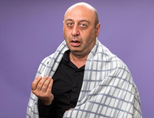コピースペースと紫色の壁に分離された温度計を保持している格子縞に包まれた痛む大人の病気の白人男性