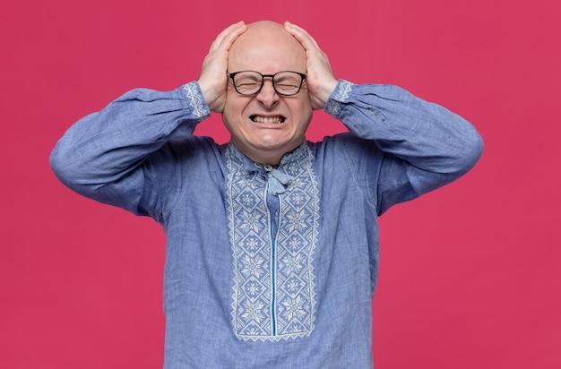 Больной взрослый славянский мужчина в синей рубашке в оптических очках держит стоя за голову