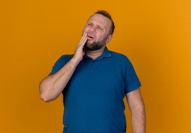 Больной взрослый славянский мужчина смотрит в сторону, положив руку на подбородок, страдая от зубной боли