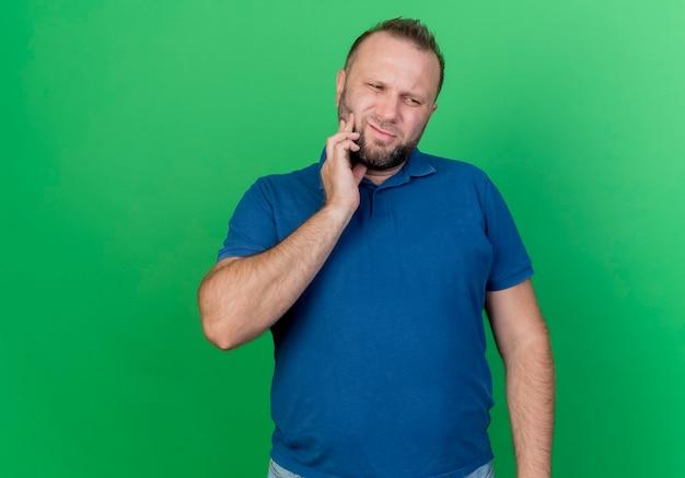 Uomo slavo adulto dolorante che guarda al lato che tocca la guancia che soffre di mal di denti isolato sulla parete verde con lo spazio della copia