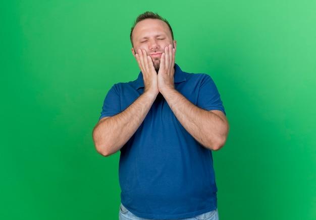 복사 공간이 녹색 벽에 고립 된 닫힌 된 눈으로 치통으로 고통받는 얼굴에 손을 댔을 아픈 성인 슬라브 남자