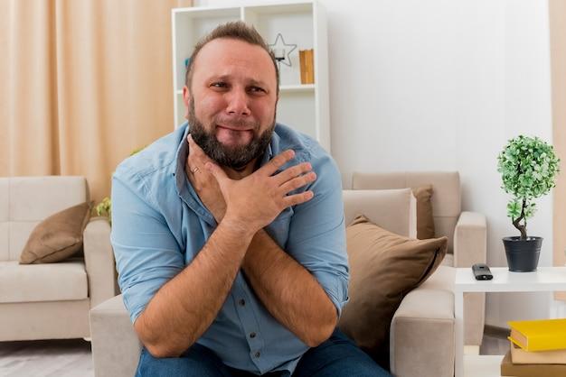 아픈 성인 슬라브 남자는 거실 안에 두 손으로 목을 잡고 안락 의자에 앉아 있습니다.