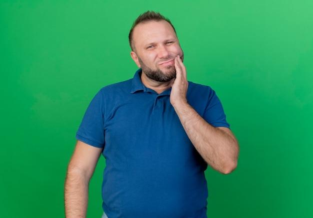 Uomo slavo adulto dolorante che tocca la guancia che soffre di mal di denti isolato sulla parete verde con lo spazio della copia