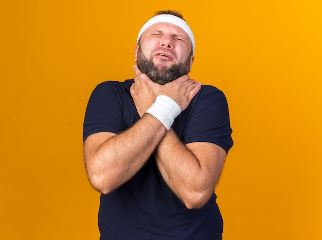 Aching adult slavic sporty man wearing headband and wristbands choking himself with hands isolated on orange wall with copy space