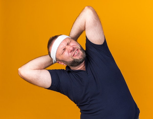 Aching adult slavic sporty man wearing headband and wristbands holding head behind isolated on orange wall with copy space