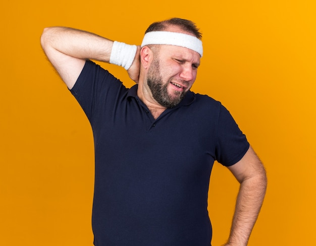 Aching adult slavic sporty man wearing headband and wristbands puts hand on neck behind isolated on orange wall with copy space