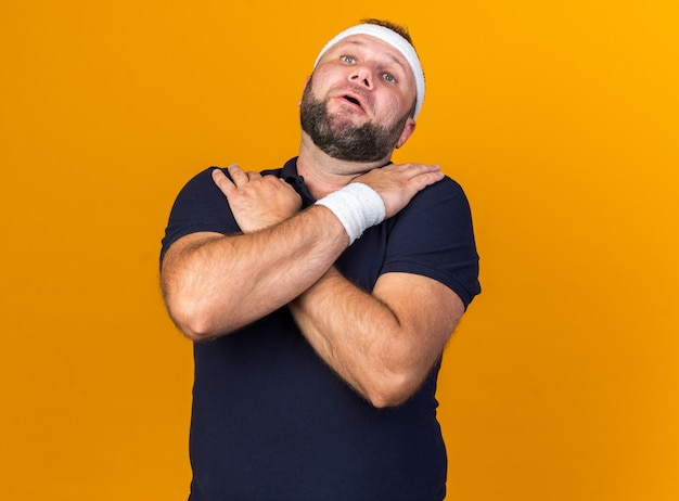 Aching adult slavic sporty man wearing headband and wristbands puts hands on his shoulders isolated on orange wall with copy space