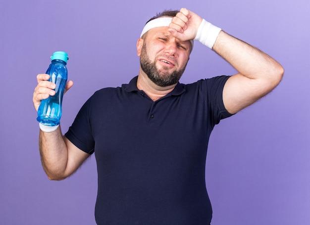 Dolorante adulto slavo sportivo uomo che indossa la fascia e braccialetti mettendo la mano sulla fronte e tenendo la bottiglia di acqua isolata sul muro viola con spazio di copia