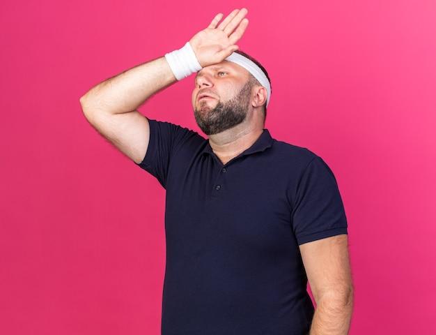 Uomo sportivo slava adulto dolorante che indossa fascia e braccialetti mettendo la mano sulla fronte isolata sulla parete rosa con spazio di copia
