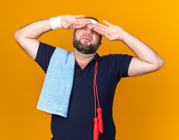 Aching adult slavic sporty man with jumping rope around neck wearing headband and wristbands holding towel on shoulder and putting hands on forehead isolated on orange wall with copy space