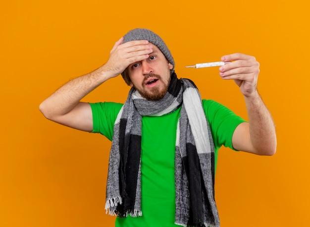 冬の帽子とスカーフを身に着けている痛くて感動した若いハンサムな病気の男は、オレンジ色の壁で隔離された額に手を保ちながら、正面を見て温度計を保持しています