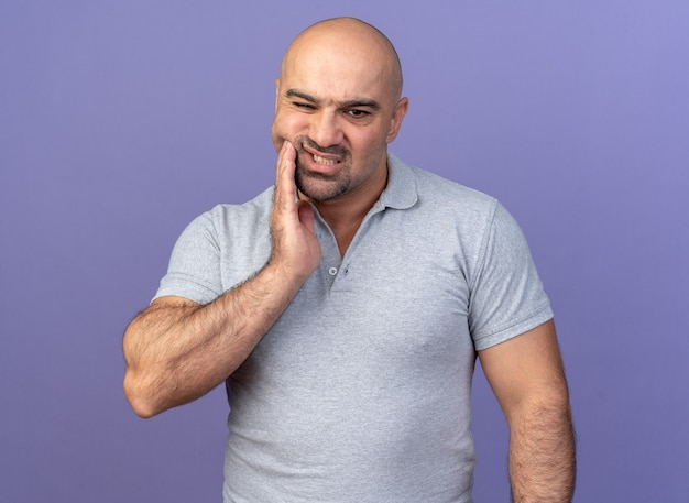 Aching casual middle-aged man keeping hand on cheek looking down suffering from toothache isolated on purple wall