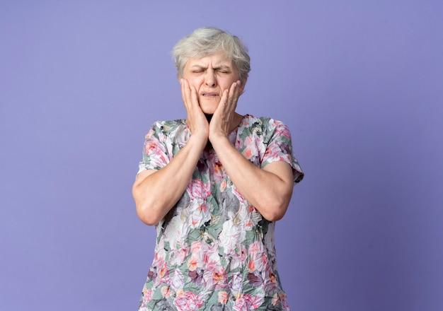 아프고 노인 여성이 보라색 벽에 고립 된 얼굴에 손을 넣습니다.