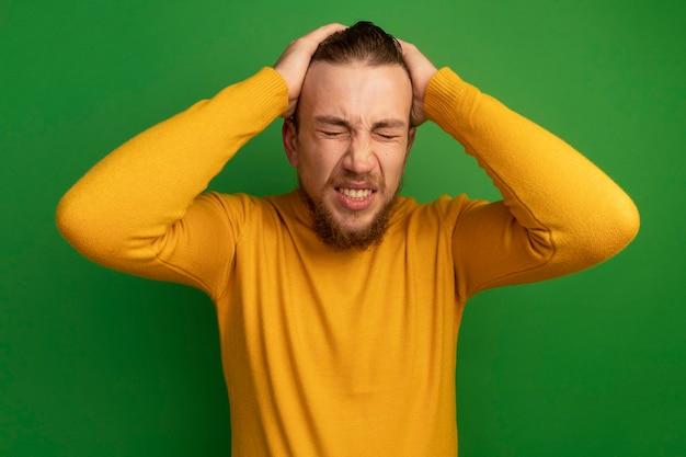 아프고 잘 생긴 금발의 남자는 녹색에 두 손으로 머리를 보유