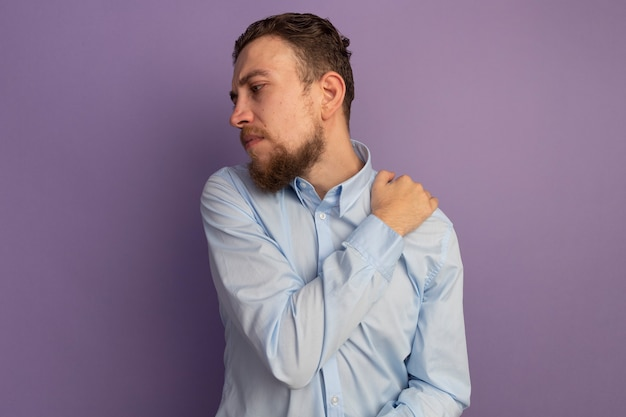 L'uomo biondo bello dolorante tiene la spalla che esamina il lato isolato sulla parete viola