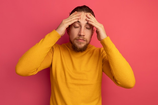 아프고 잘 생긴 금발의 남자는 분홍색에 이마에 손을 넣습니다