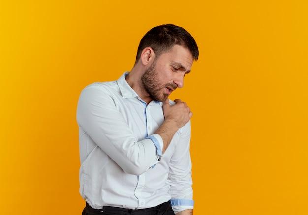 L'uomo bello dolorante tiene la spalla guardando in basso isolato sulla parete arancione