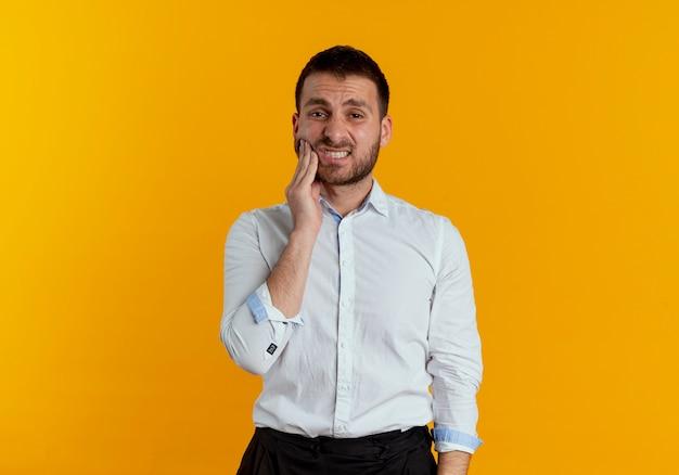 아프고 잘 생긴 남자가 오렌지 벽에 고립 된 얼굴에 손을 넣습니다.