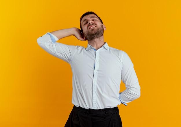 아프고 잘 생긴 남자가 뒤에 머리에 손을 대고 오렌지 벽에 고립 된 뒤로 보유