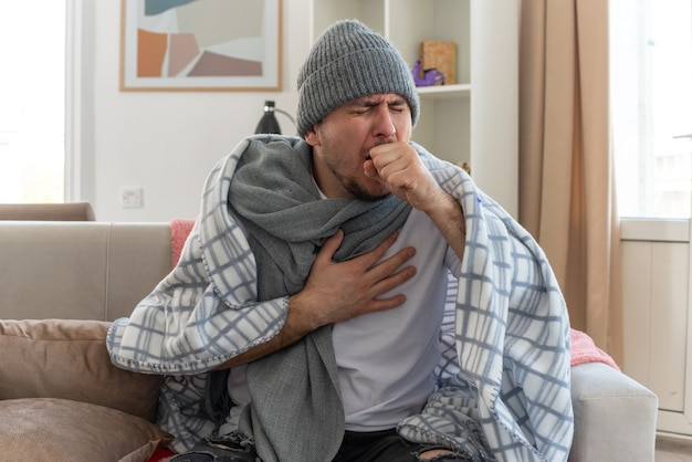 Uomo malato dolorante con sciarpa intorno al collo che indossa cappello invernale avvolto in plaid tosse tenendo il pugno vicino alla bocca seduto sul divano in soggiorno