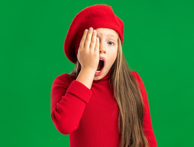 Aching little blonde girl wearing red beret keeping hand on eye with open mouth isolated on green wall with copy space