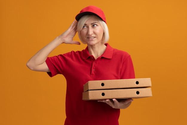 Donna bionda di mezza età dolorante delle consegne in uniforme rossa e cappuccio che tiene i pacchetti di pizza guardando il lato che tocca la testa