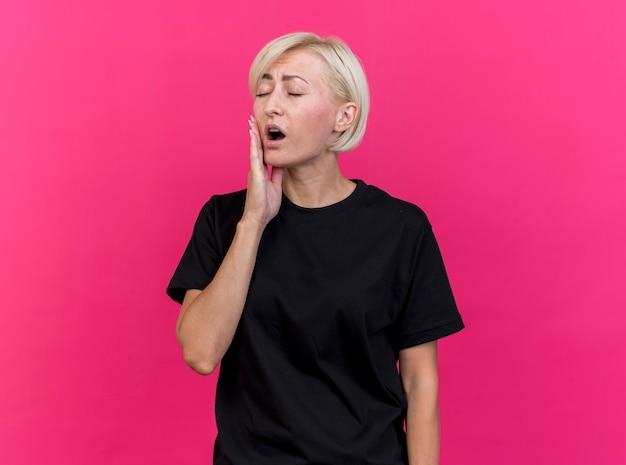 분홍색 벽에 고립 된 치통을 앓고 닫힌 눈을 가진 뺨을 만지고 아픈 중년 금발의 여자