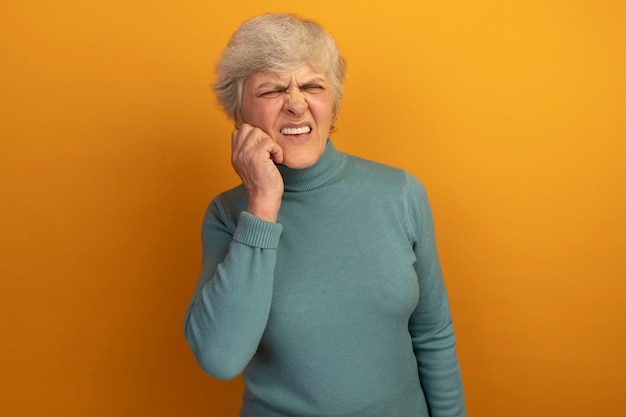 Aching old woman wearing blue turtleneck sweater looking at side touching cheek suffering from toothache isolated on orange wall with copy space