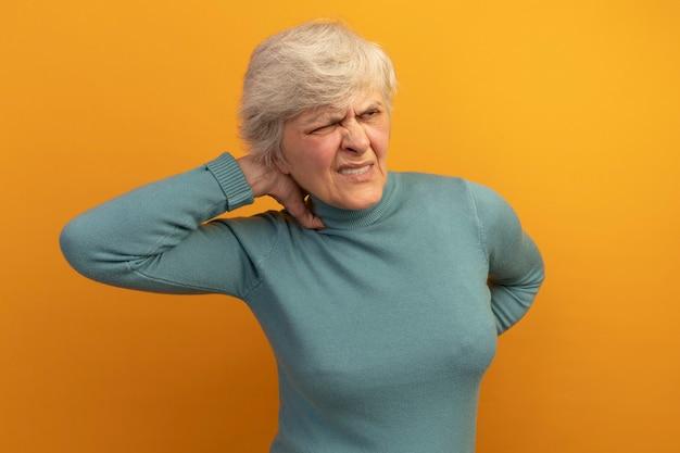 Donna anziana dolorante che indossa un maglione blu a collo alto mettendo la mano dietro il collo e sulla schiena guardando di lato con un occhio chiuso