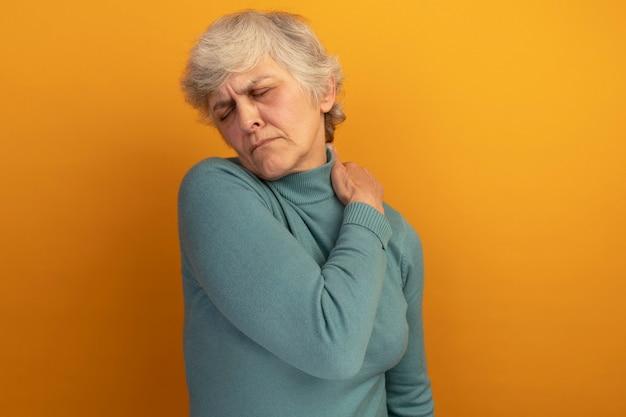 Donna anziana dolorante che indossa un maglione blu a collo alto che mette la mano sulla spalla con gli occhi chiusi