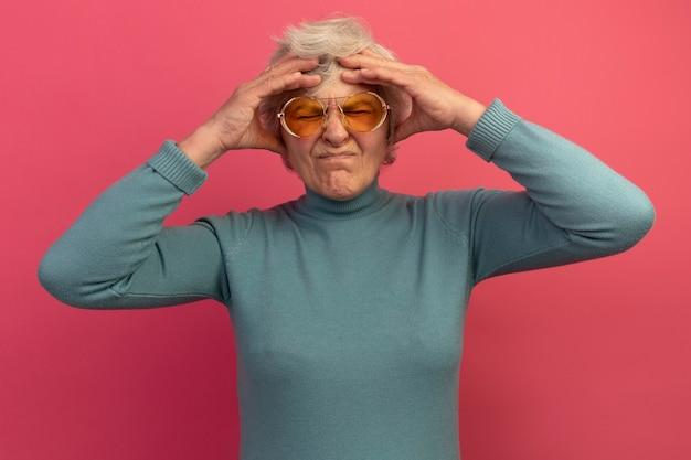 Una donna anziana dolorante che indossa un maglione blu a collo alto e occhiali da sole che tiene le mani sulla testa soffre di mal di testa con gli occhi chiusi