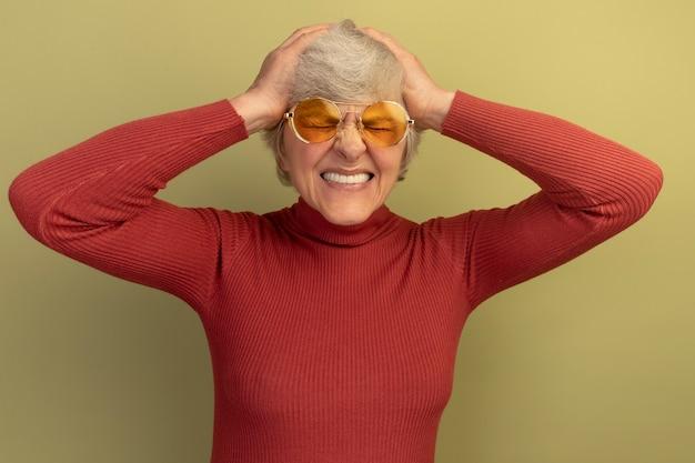 Donna anziana dolorante che indossa un maglione a collo alto rosso e occhiali da sole che tiene le mani sulla testa soffre di mal di testa con gli occhi chiusi isolati sul muro verde oliva