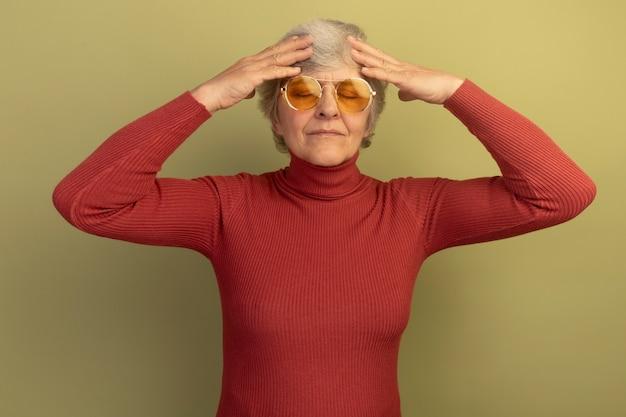 Donna anziana dolorante che indossa un maglione a collo alto rosso e occhiali da sole che tiene le mani sulla testa con gli occhi chiusi isolati sul muro verde oliva