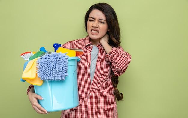 Donna delle pulizie caucasica dolorante che tiene in mano l'attrezzatura per la pulizia e le tiene il collo