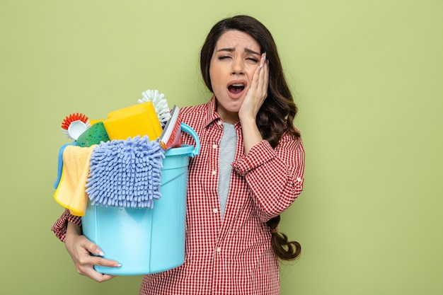 Donna abbastanza caucasica dolorante delle pulizie che tiene in mano l'attrezzatura per la pulizia e si mette la mano sul viso