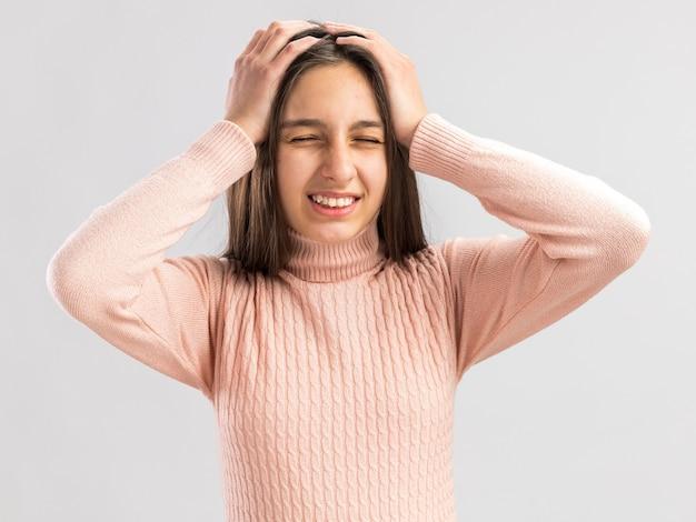 Adolescente graziosa dolorante che tiene le mani sulla testa con gli occhi chiusi che mostra i denti isolati sul muro bianco