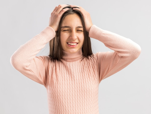 흰 벽에 격리된 이빨을 보여주는 눈을 감고 머리에 손을 얹고 있는 아픈 예쁜 10대 소녀