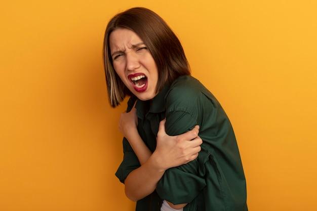 아프다 예쁜 여자 팔을 보유하고 오렌지 벽에 고립 된 비명