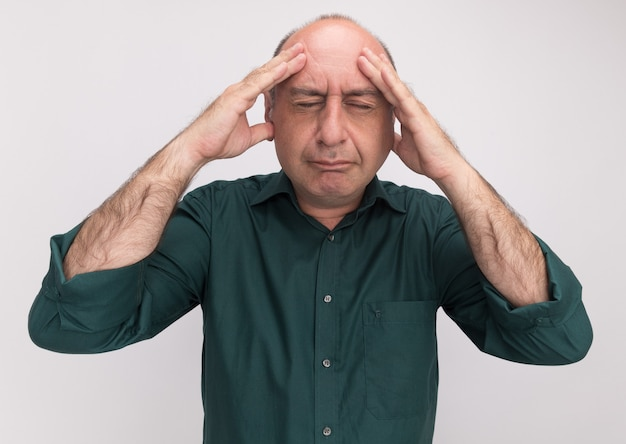 Aching with closed eyes middle-aged man wearing green t-shirt putting hand on forehead isolated on white wall