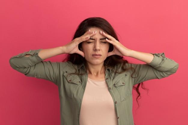 분홍색 벽에 고립 된 사원에 손을 댔을 올리브 녹색 티셔츠를 입고 눈을 감고 젊은 아름 다운 소녀 아프다