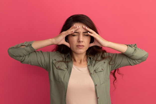 Dolorante con gli occhi chiusi giovane bella ragazza che indossa la maglietta verde oliva che mette le mani sul tempio isolato sul muro rosa