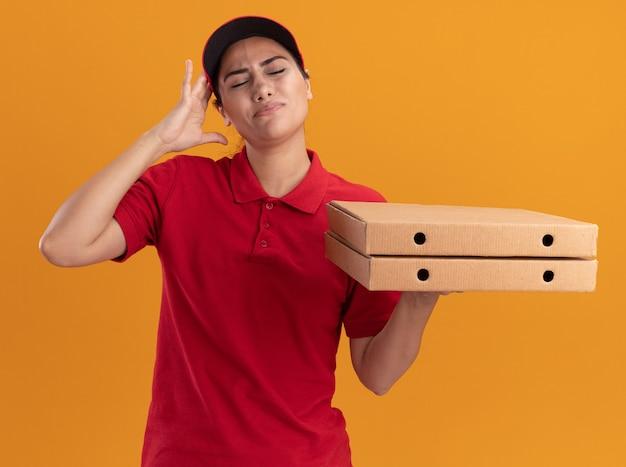 Молодая доставщица с закрытыми глазами в униформе и кепке держит коробки для пиццы, положив руку на голову, изолированную на оранжевой стене