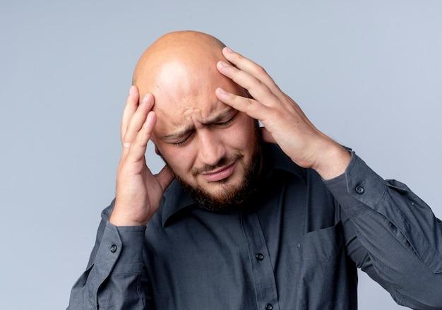白で隔離の目を閉じて頭痛に苦しんで頭を抱えている若いハゲのコールセンターの男性