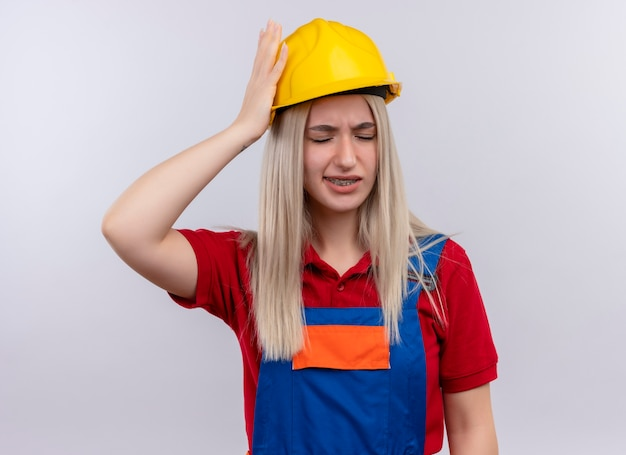 Aching young blonde engineer builder girl in uniform in dental braces putting hand on head having headache with closed eyes on isolated white space