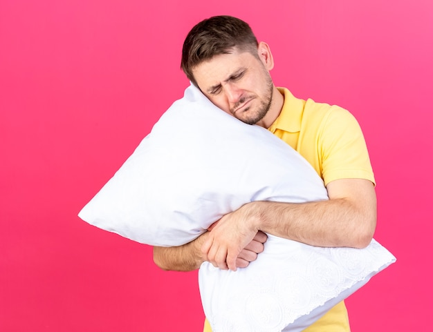 Aching young blonde ill man hugs and puts head on pillow isolated on pink wall