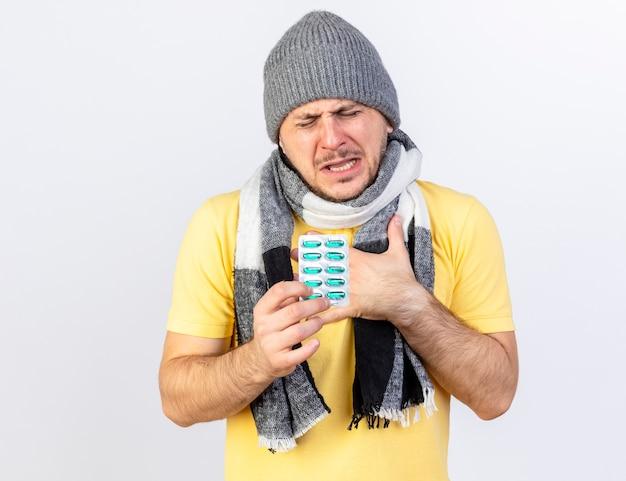 Больной молодой блондин в зимней шапке и шарфе кладет руку на грудь и держит упаковку медицинских таблеток, изолированную на белой стене