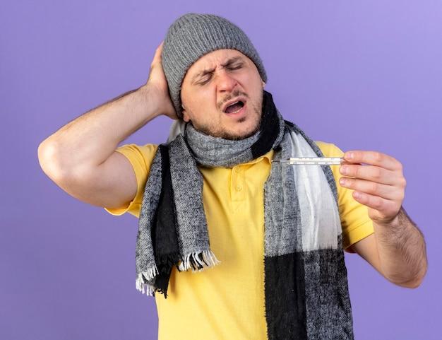 겨울 모자와 스카프를 착용하고 아픈 젊은 금발의 아픈 남자는 보라색 벽에 고립 된 온도계를보고 뒤에 머리에 손을 넣습니다