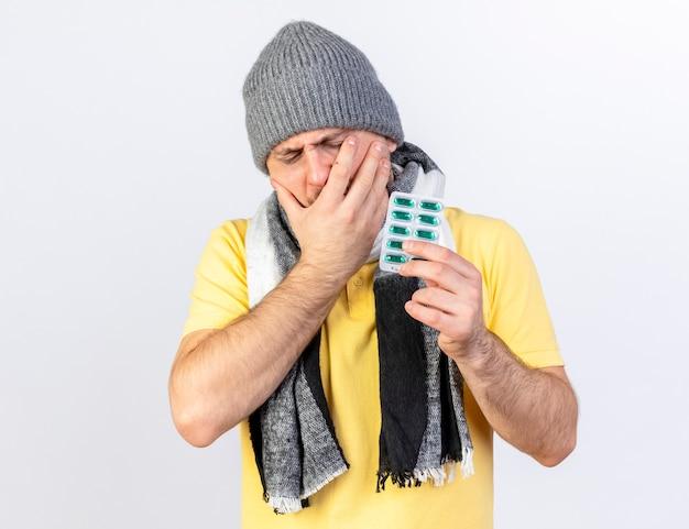 Il giovane uomo malato biondo dolorante che indossa il cappello e la sciarpa di inverno mette la mano sul fronte e tiene il pacchetto delle pillole mediche isolate sulla parete bianca