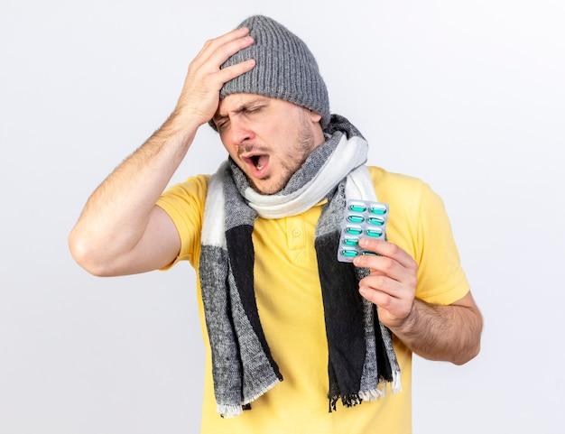 겨울 모자와 스카프를 착용하는 젊은 금발의 아픈 슬라브 남자가 머리에 손을 넣고 복사 공간이 흰 벽에 고립 된 의료 약의 팩을 보유하고 있습니다.