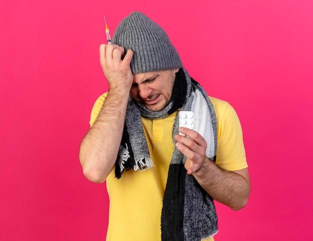 겨울 모자와 스카프를 착용하는 젊은 금발의 아픈 슬라브 남자가 주사기를 들고 머리에 손을 넣습니다.